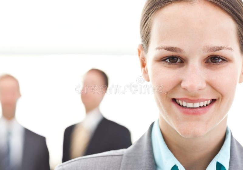 Donna di affari che propone davanti a due uomini d'affari immagini stock