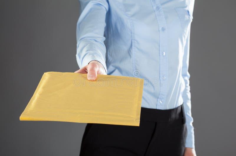 Donna di affari che raggiunge fuori lettera in busta gialla fotografia stock