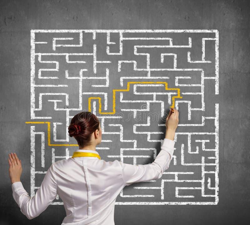 Donna di affari che risolve problema del labirinto immagini stock