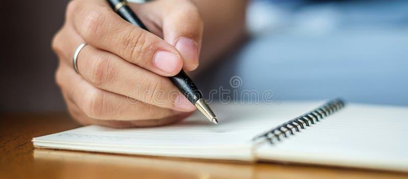 Donna di affari che scrive qualcosa sul taccuino nell'ufficio, mano della penna di tenuta della donna con la firma sul rapporto d fotografie stock libere da diritti