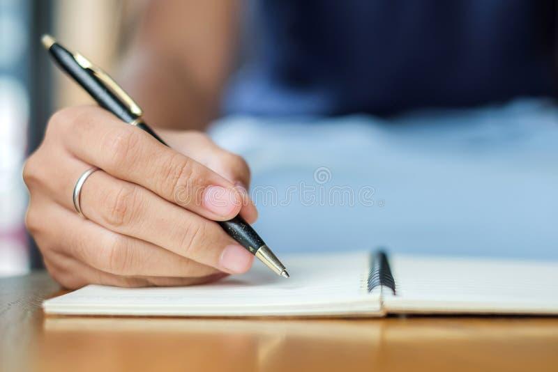 Donna di affari che scrive qualcosa sul taccuino nell'ufficio, mano della penna di tenuta della donna con la firma sul rapporto d immagini stock