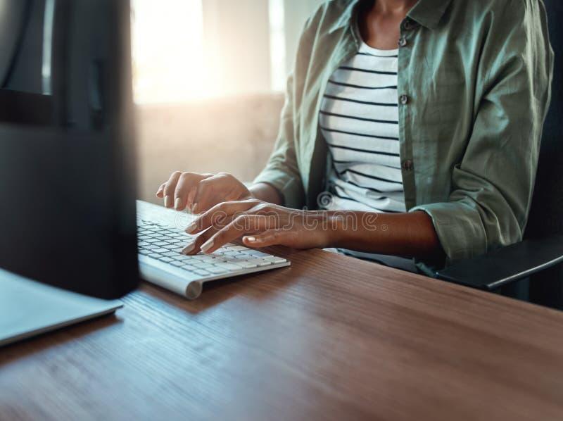 Donna di affari che scrive sulla tastiera all'interno in una costruzione moderna fotografie stock libere da diritti