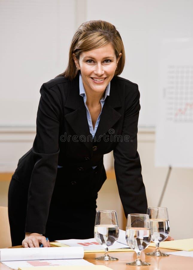 Donna di affari che si appoggia sulla tabella nella sala per conferenze immagini stock