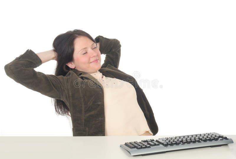 Donna di affari che si distende allo scrittorio immagine stock