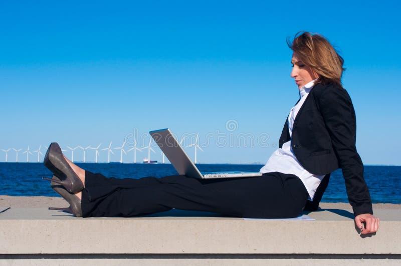 Donna di affari che si distende con il computer portatile fotografia stock libera da diritti