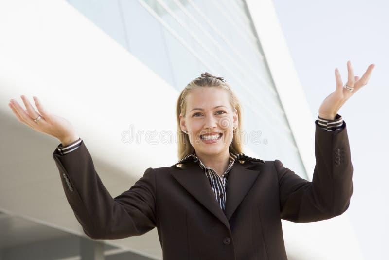 Donna di affari che si leva in piedi all'aperto dalla costruzione fotografia stock