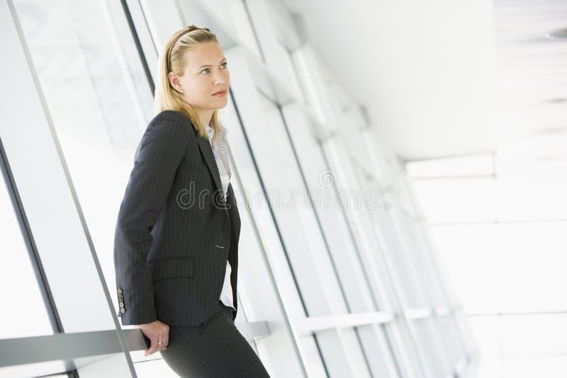 Donna di affari che si leva in piedi in corridoio fotografia stock