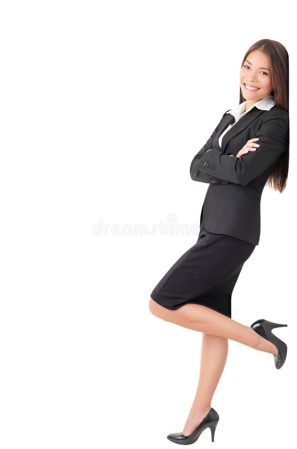 Donna di affari che si leva in piedi pendente sul segno immagini stock