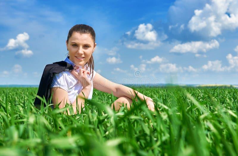Donna di affari che si rilassa in sole di sotto all'aperto del campo di erba verde La bella ragazza si è vestita in vestito che r immagini stock libere da diritti