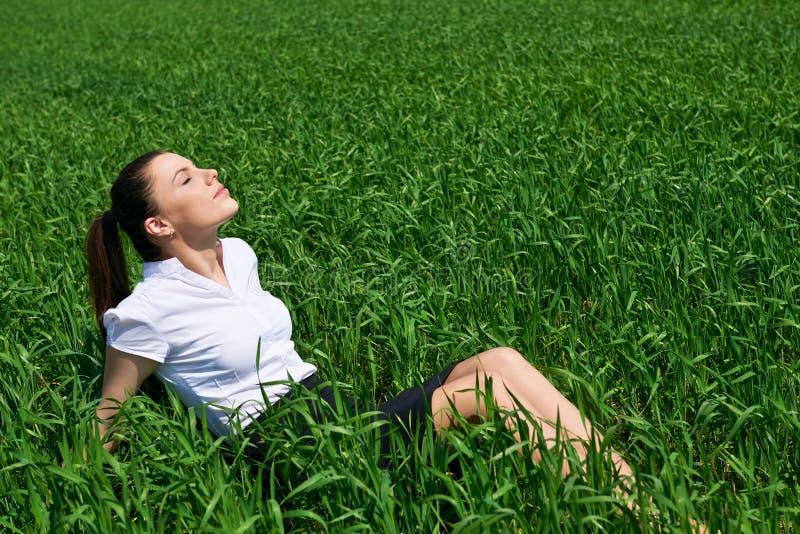Donna di affari che si rilassa in sole di sotto all'aperto del campo di erba verde La bella ragazza si è vestita in vestito che r immagini stock