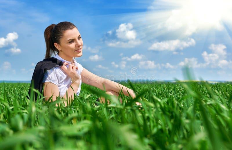 Donna di affari che si rilassa in sole di sotto all'aperto del campo di erba verde La bella ragazza si è vestita in vestito che r immagine stock libera da diritti