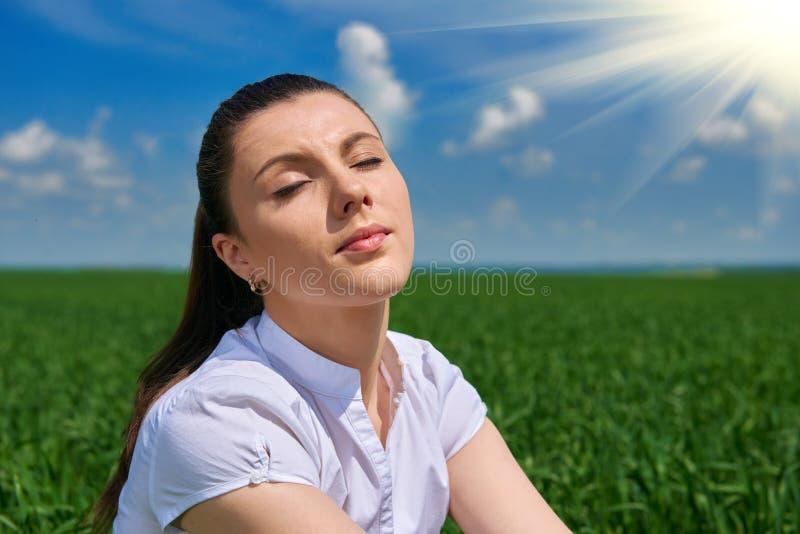Donna di affari che si rilassa in sole di sotto all'aperto del campo di erba verde La bella ragazza si è vestita in vestito che r fotografie stock libere da diritti
