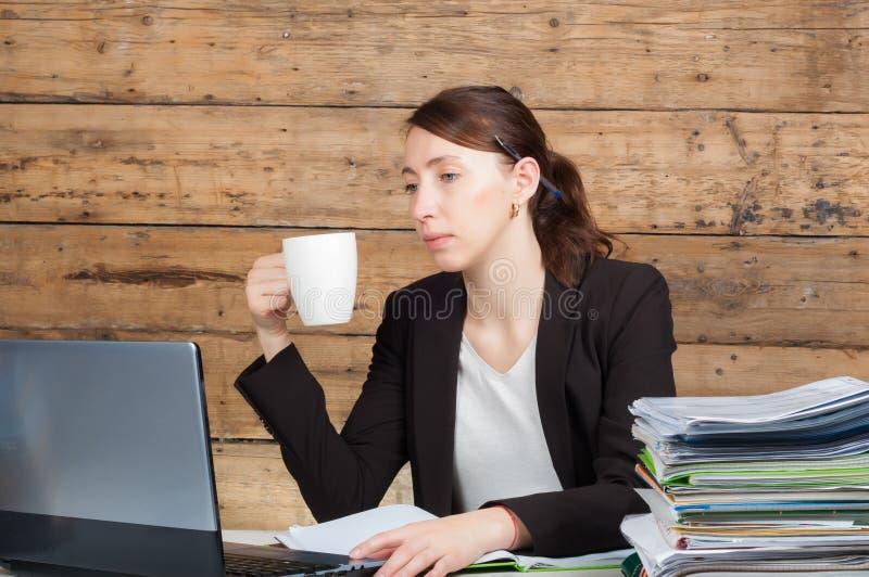 Donna di affari che si siede al suo scrittorio e che lavora alla tenuta del computer portatile fotografia stock libera da diritti