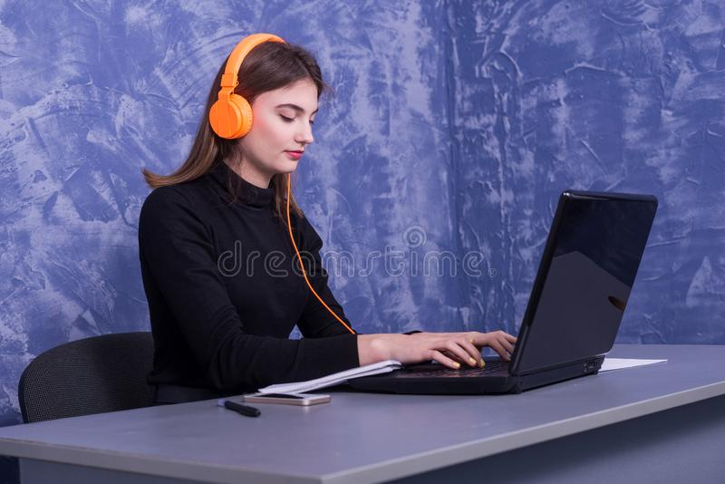 Donna di affari che si siede in cuffie e che lavora ad un computer portatile, lavoro distante immagini stock libere da diritti