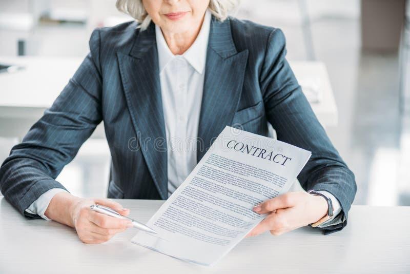 Donna di affari che si siede nel luogo di lavoro e che indica al contratto fotografie stock