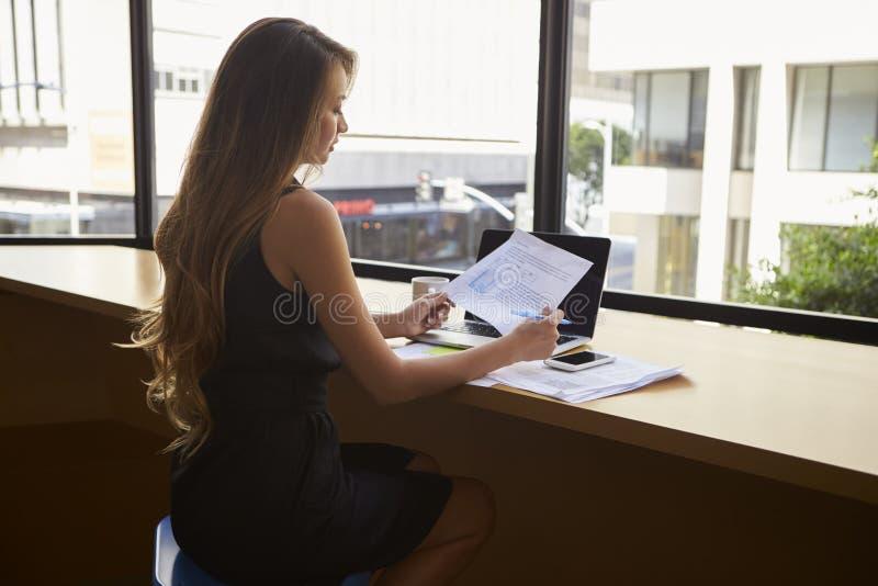 Donna di affari che si siede nell'ufficio moderno che legge un documento fotografia stock