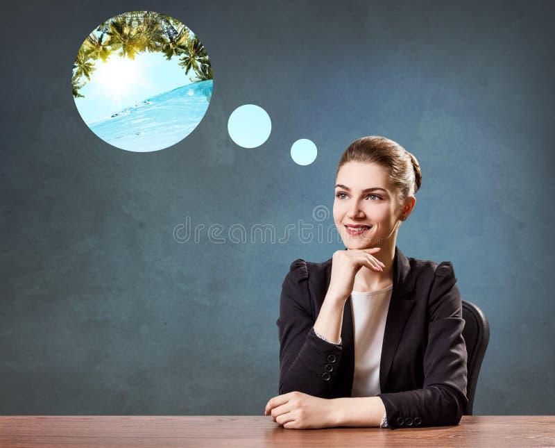 Donna di affari che si siede nell'ufficio che sogna della vacanza immagini stock