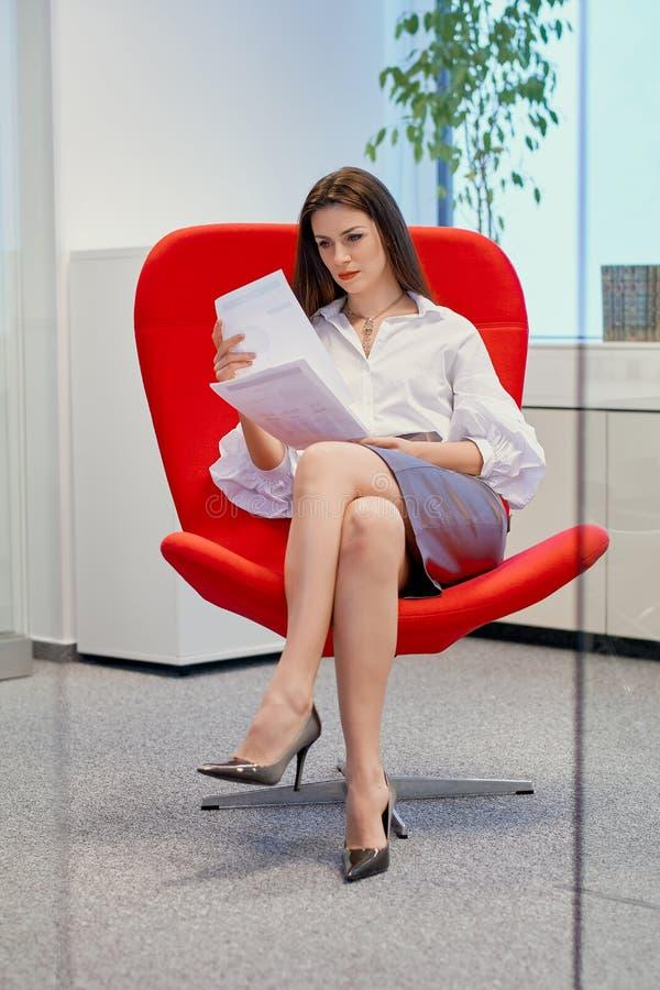 Donna di affari che si siede su una sedia rossa in un ufficio di vetro e nei documenti dei controlli fotografia stock libera da diritti