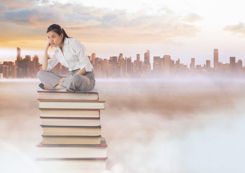 Donna di affari che si siede sui libri impilati dalla città distante immagini stock