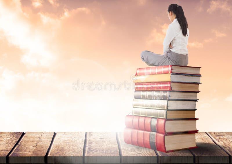 Donna di affari che si siede sui libri impilati dalle nuvole soleggiate fotografia stock libera da diritti