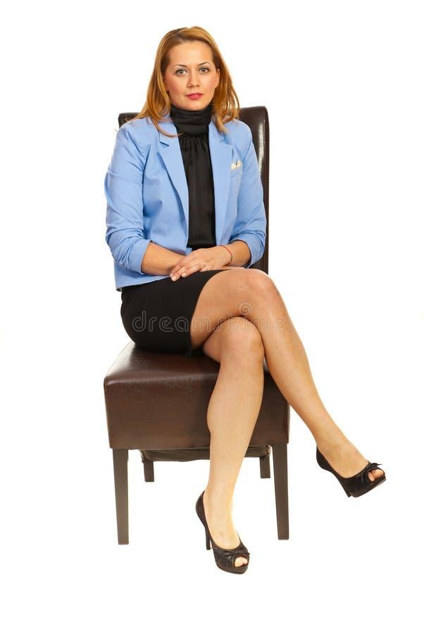Donna di affari che si siede sulla presidenza immagini stock libere da diritti