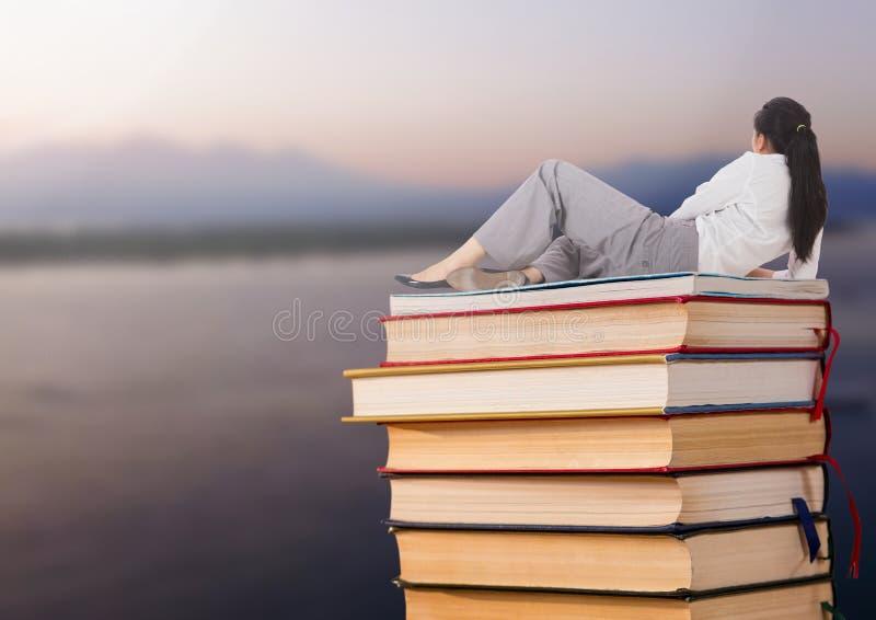 Donna di affari che si trova sui libri impilati dal lago del mare fotografie stock