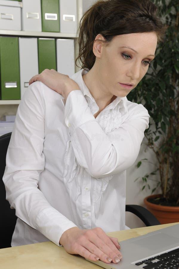 Donna di affari che soffre dal dolore al collo severo immagini stock libere da diritti