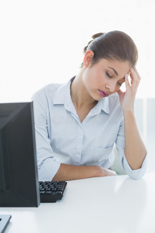 Donna di affari che soffre dall'emicrania davanti al computer fotografie stock