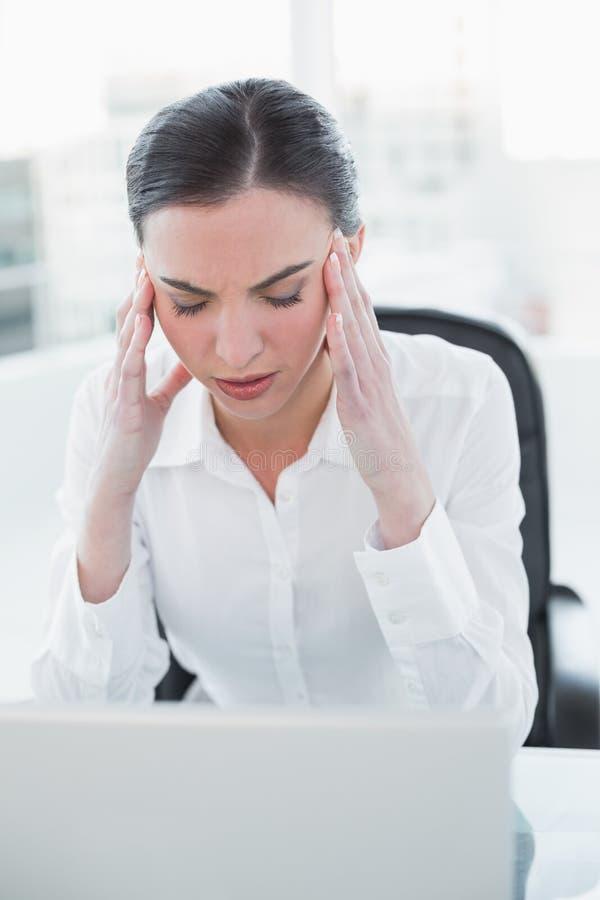 Donna di affari che soffre dall'emicrania davanti al computer portatile fotografia stock