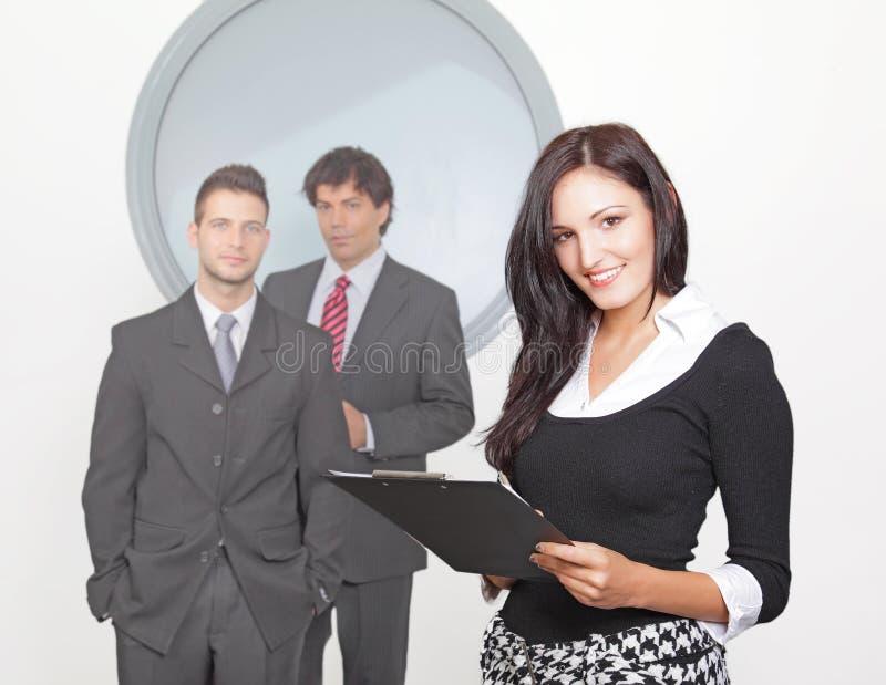 Donna di affari che sorride con il collega nel backgr fotografia stock libera da diritti