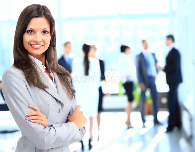 Donna di affari che sta con il suo personale nel fondo all'ufficio fotografie stock libere da diritti