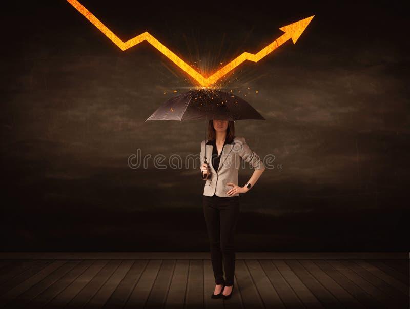 Donna di affari che sta con l'ombrello che tiene freccia arancio fotografia stock libera da diritti