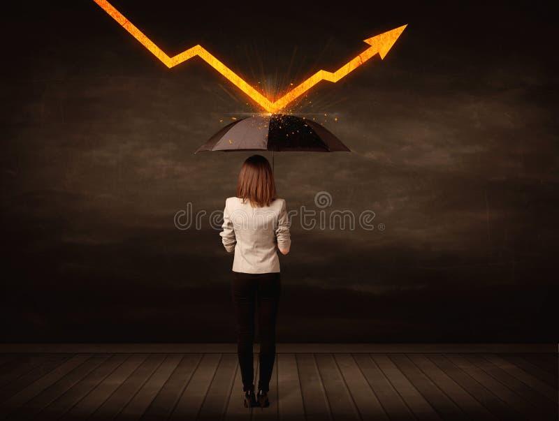 Donna di affari che sta con l'ombrello che tiene freccia arancio fotografie stock
