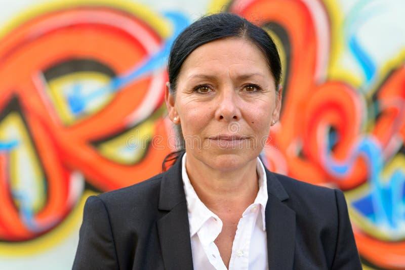 Donna di affari che sta davanti ai graffiti fotografia stock