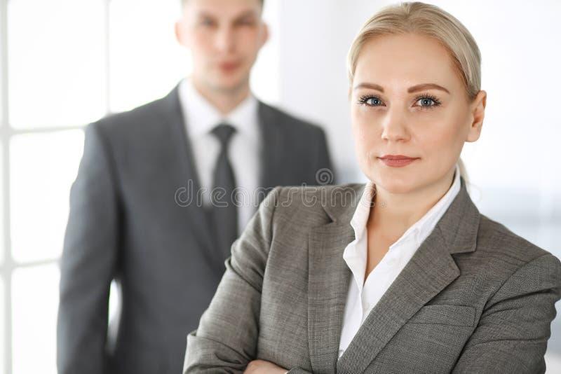 Donna di affari che sta diritto con l'uomo d'affari del collega in ufficio, colpo in testa Successo ed associazione corporativa immagine stock libera da diritti