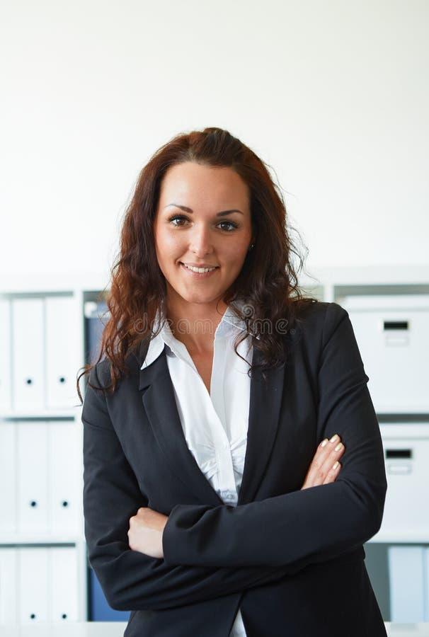 Donna di affari che sta nell'ufficio fotografia stock