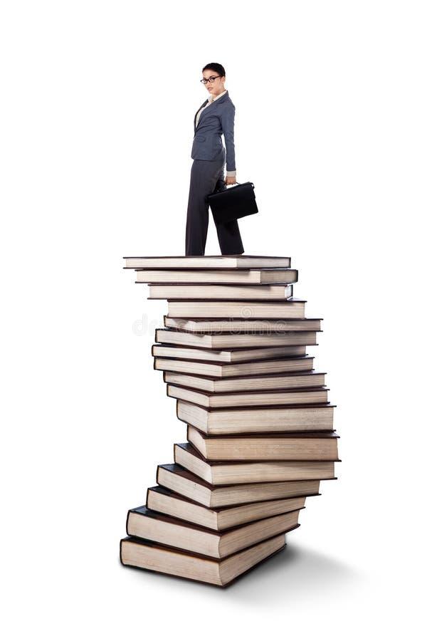 Donna di affari che sta su una pila di libri immagine stock