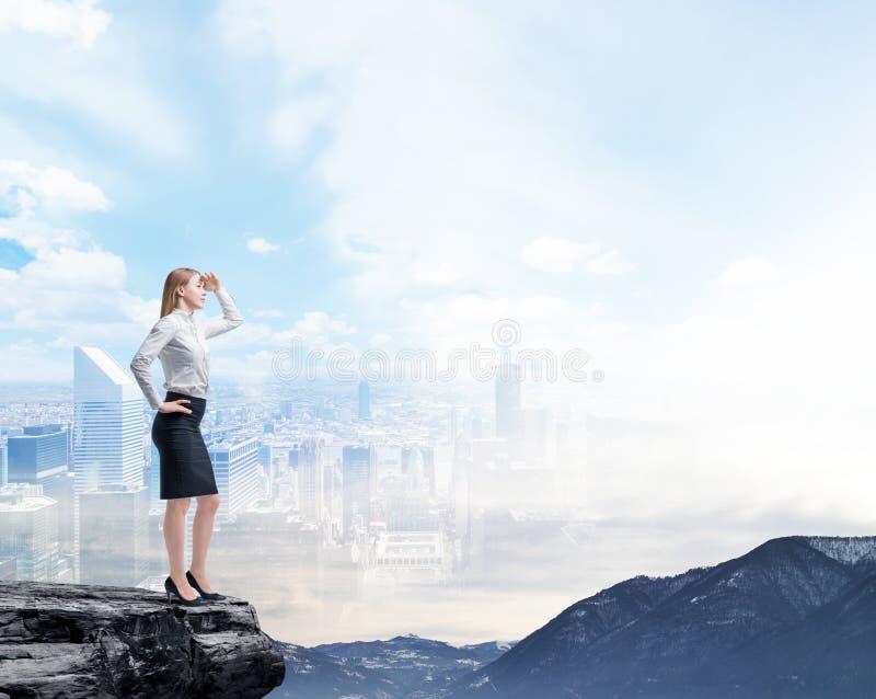 Donna di affari che sta su una roccia e che esamina la città di affari di volo immagine stock libera da diritti