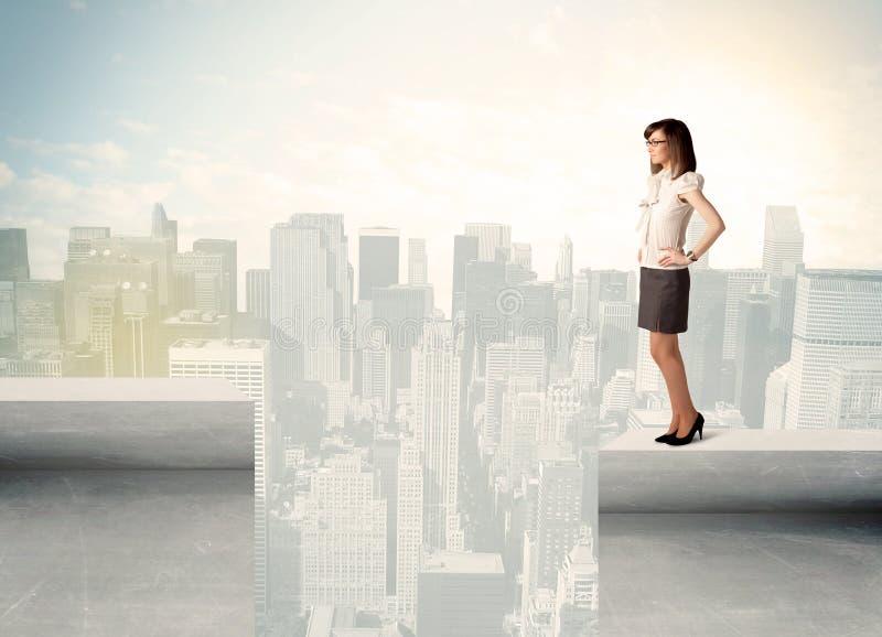 Donna di affari che sta sull'orlo del tetto immagini stock libere da diritti