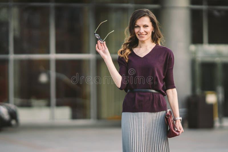 Donna di affari che sta sulla via contro l'edificio per uffici Funzionamento della donna di affari della citt? Sorridere della do fotografia stock libera da diritti