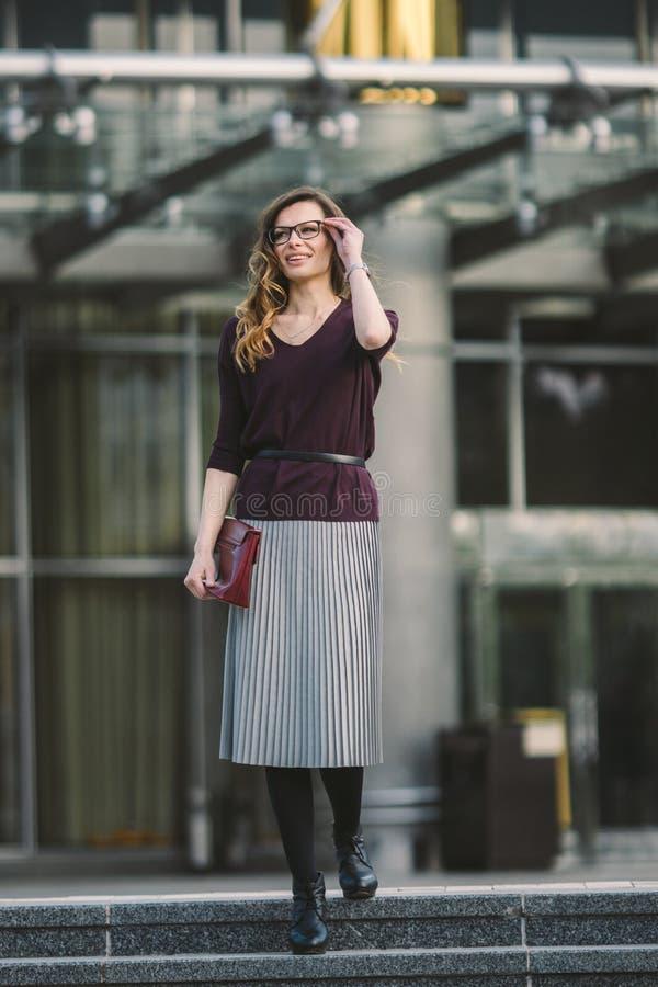 Donna di affari che sta sulla via contro l'edificio per uffici Funzionamento della donna di affari della citt? Sorridere della do fotografia stock