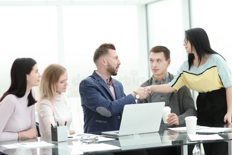 Donna di affari che stringe le mani con il project manager vicino al desktop fotografie stock