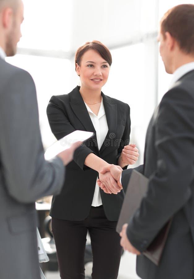 Donna di affari che stringe le mani con un businssman nel corso di una riunione fotografie stock
