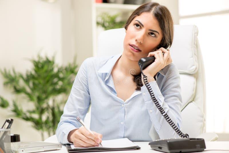 Donna di affari che telefona nell'ufficio fotografia stock libera da diritti