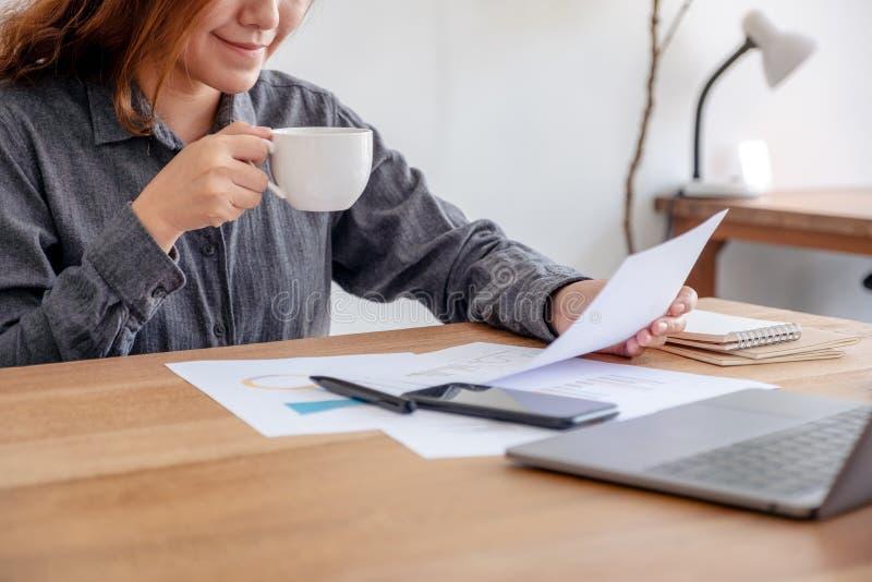 Donna di affari che tiene e che esamina i dati di gestione e documento con il computer portatile sulla tavola mentre bevendo caff fotografia stock libera da diritti