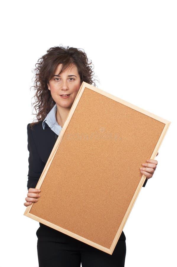 Donna di affari che tiene il corkboard fotografia stock