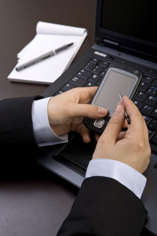 Donna di affari che tiene il telefono mobile moderno di pda fotografia stock