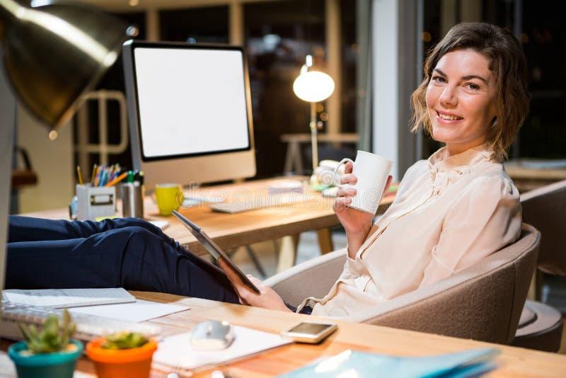 Donna di affari che tiene la tazza digitale di caffè e della compressa al suo scrittorio immagine stock
