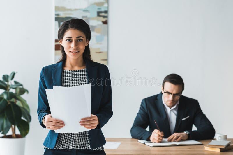 Donna di affari che tiene le carte mentre uomo che lavora dalla tavola con il blocco note immagini stock libere da diritti