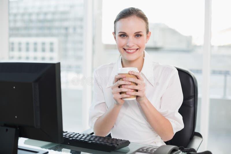 Donna di affari che tiene tazza eliminabile che sorride alla macchina fotografica immagini stock libere da diritti